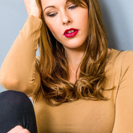 Young Woman Looking Stressed Thoughful And Depressed Sitting Down Leaning Against A Wall Alone Stock Photo