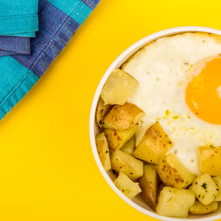Fried Egg With Fried Potatoes Breakfast In A Bowl Against A Yellow Background