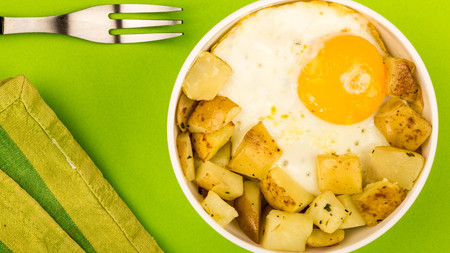 Fried Egg With Fried Potatoes Breakfast In A Bowl Against A Green Background