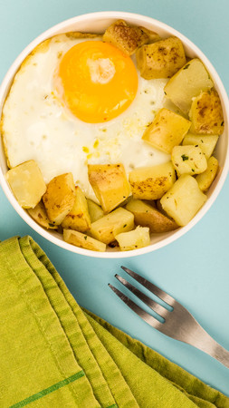 Fried Egg With Fried Potatoes Breakfast In A Bowl Blue Background Stock Photo