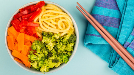 Healthy Vegetarian Hawaiian Style Buddha Food Bowl With Broccoi Carrots Red Peppers and Egg Noodles Against A Blue Background