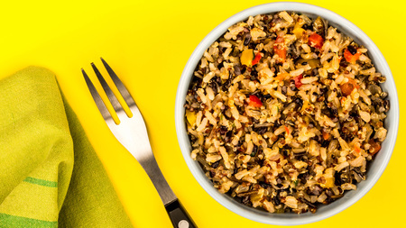 Healthy Vegetarian Or Vegan Meal Of Rice And Quinoa Against A Yellow Background