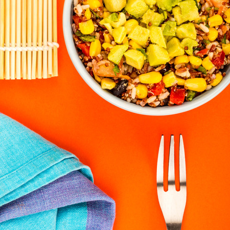 Vegetarian Or Vagan Mexican Style Rice And Avocado Salad Against A Red Background Stock Photo