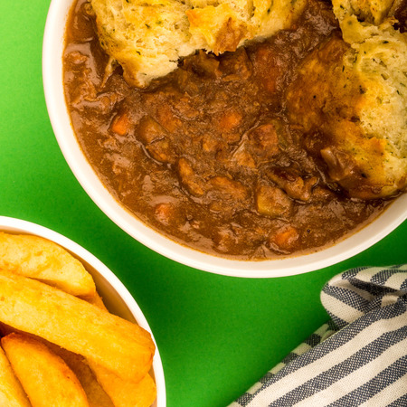 Traditional British Beef Casserole With Dumplings Against A Green Background And A Bowl Of Chips Stock Photo