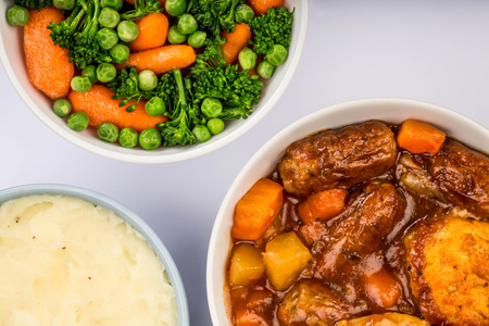 Traditional British Lincolnshire Sausage Cobbler Against A Pale Blue Background With A Bowl Of Mashed Potatoes And Mixed Vegetables