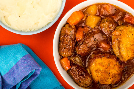 Traditional British Lincolnshire Sausage Cobbler Against A Red Background With A Bowl Of Mashed Potatoes