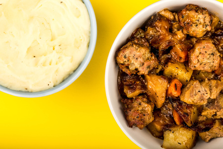 British Or English Style Slow Roasted Pulled Pork And Stuffing Casserole Against A Yellow Background With A Bowl Of Mashed Potatoes
