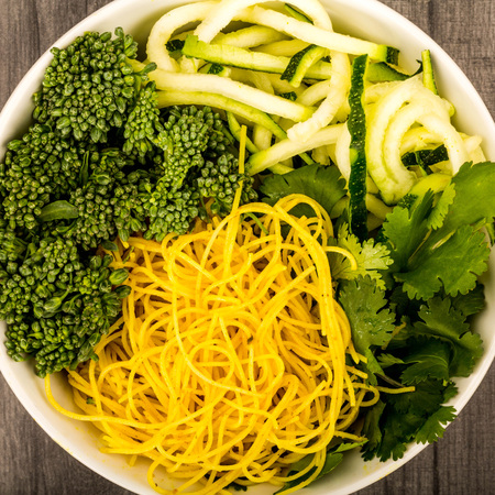 Healthy Vegetarian Or Vegan Noodle Buddha Bowl With Courgettes Broccoli And Coriander On A Dark Wooden Kitchen Table Top Stock Photo