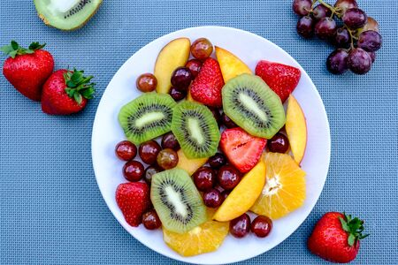 Healthy Vegetarian Fresh Fruit Summer Salad Dessert With Oranges, Strawberries, Kiwi Fruit Peaches and Grapes