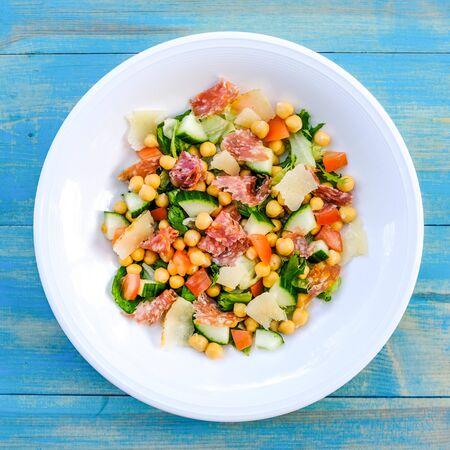 Verse Gezonde Salami Worstsalade Met Kikkererwten, Tomaten, Komkommer En Sla Stockfoto