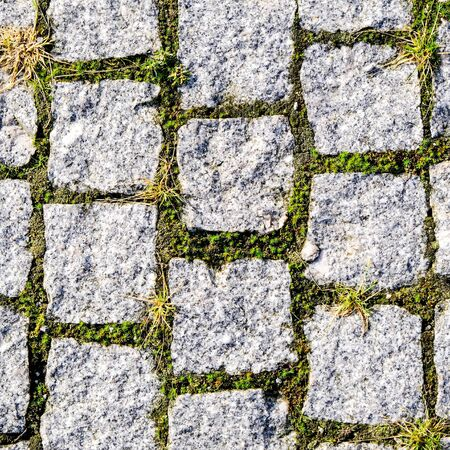 Stone Pathway Walkway or Pavement Textured Background With Grass and Moss Growth In the Joints In a Flat Lay Close Up 写真素材 - 130048267