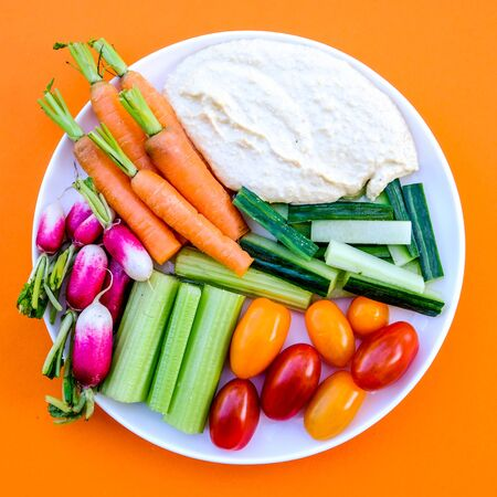 Fresh Vegetable Crudite Platter With Hummus and Baby Carrots, Radishes, Cucumber, Celery and Tomatoes