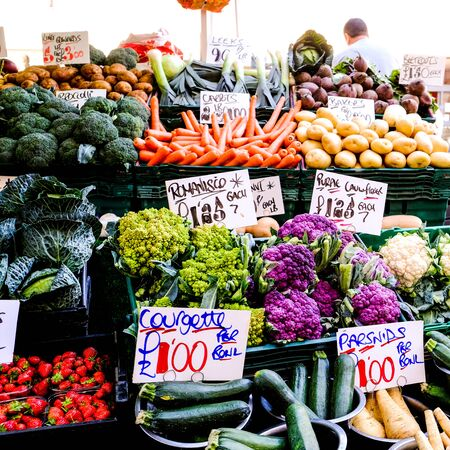Market Seller Selling Fresh Vegetables, Including Romanisco, Purple Cauliflower, Courgettes, Carrots, Potatoes, Cabbage, Parsnips and Beetroot
