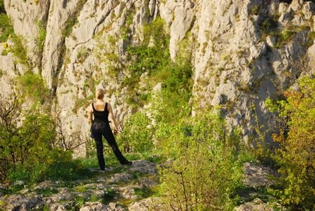 a girl is standing on a cliff photo