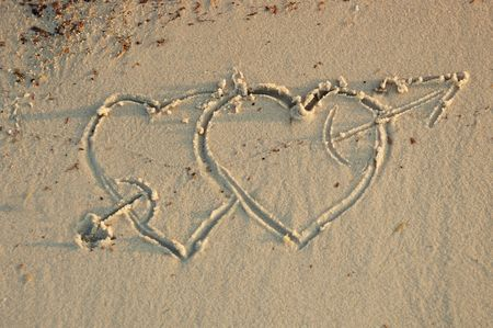 two hearts with an arrow in a sand