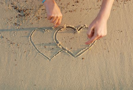 drawing hearts in a sand Stock Photo - 3338414