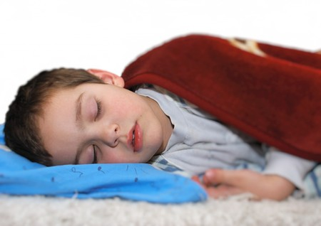boy is sleeping on a bed covered with a blanket
