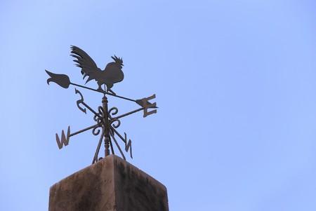 wiatrowskaz: Wiatr łopatkowych w formie z kogut na szczycie dachu Zdjęcie Seryjne