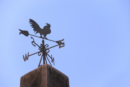 Wind vane in a form of a rooster on the top of a roof photo