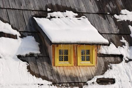 Window on old Serbian wooden house in winter