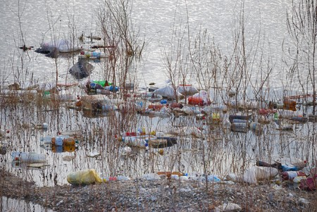 Trash floating polluting water in a pond