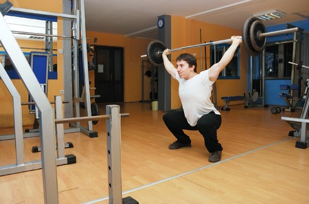 Young man in a gym at workout