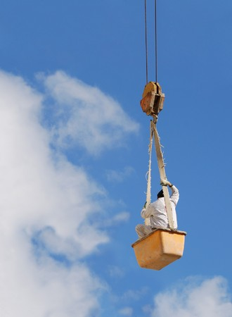 A worker hanging on a steel cable Stock Photo