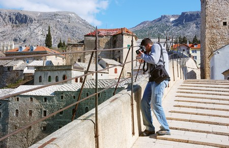 A photographer shooting from the Old Brigde in Mostar