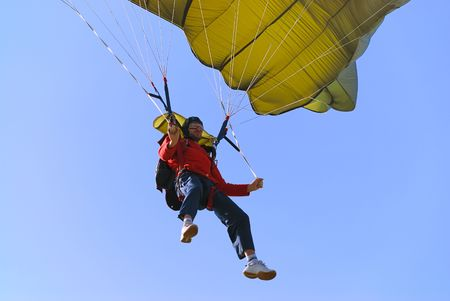 Parachutist pulling brakes of a green parachute.