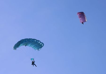 Two parachutes on a bright sunny day.