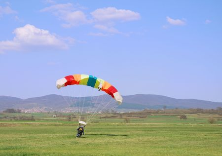 Parachutist landed on a field after good flight.