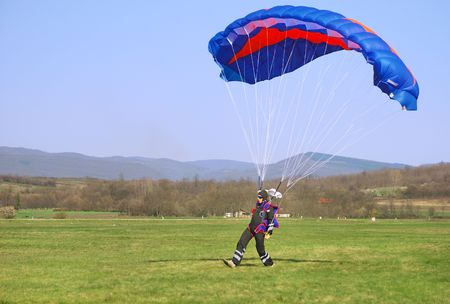 landed: Parachutist landed on a field after good flight.