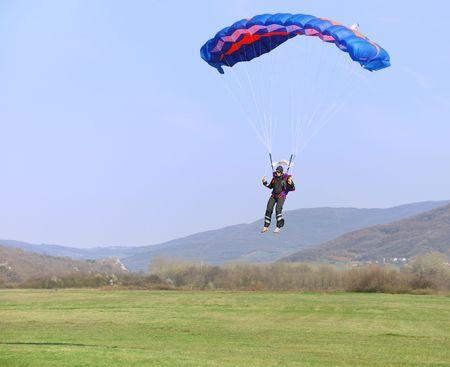 Parachutist landing on a field after good flight. Stock Photo