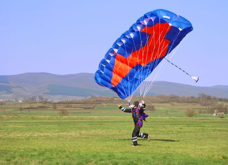 Parachutist running after landing in a field.