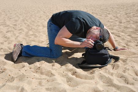 Photographer on the beach using a bag to place his camera.