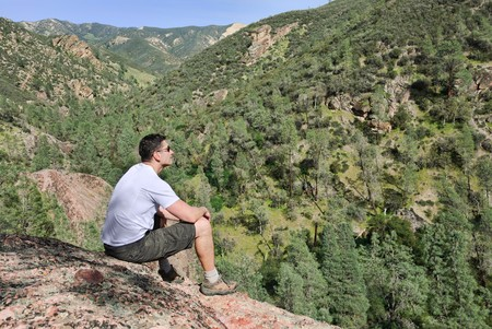 top of mountain: Handsome young man sitting on the rock enjoying the view. Stock Photo