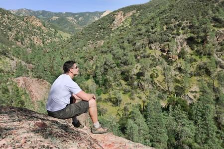 bovenaanzicht mens: Knappe jonge man zit op de rots die genieten van het uitzicht.