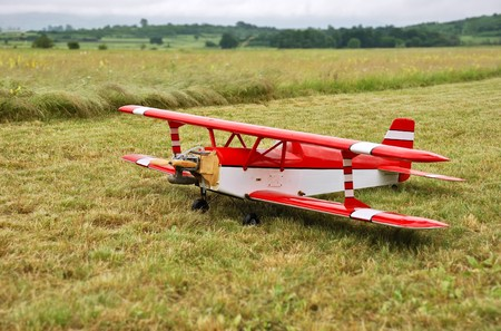 Red and white radio controlled aircraft with methanol engine on a grassy field. photo