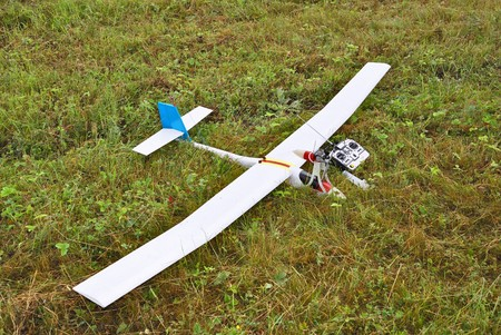 Red and white radio controlled airplane with methanol engine on a grassy field. photo