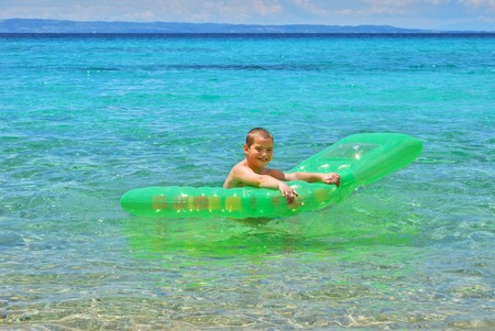 Happy boy in the sea playing with a pool float.