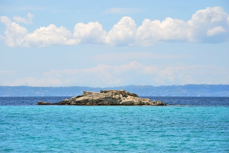 Small rocky island near Kalogria beach in Sithonia, Chalkidiki, Greece, with a view on Kassandra peninsula.