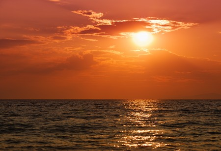 Orange sunset over Paradisos beach in Sithonia, Halkidiki, Greece. Stock Photo