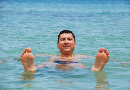 Young man floating in sea and smiling.