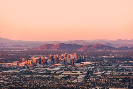 ave fenix: Phoenix Arizona con su centro iluminado por los últimos rayos de sol en el atardecer.