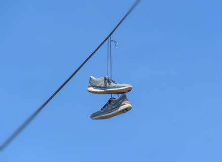 street drug: Shoes dangling on a cable over the street have many explanations, from celebrating ones birthday or wedding and making fun of drunk friends, to marking a location of drug dealers and bullying.