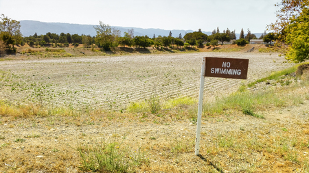 consequence: No Swimming sign next to the lake that dried out as a consequence of the drought.