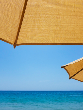 Two dark yellow sun umbrellas on the beach, the ocean and the blue sky. Banco de Imagens
