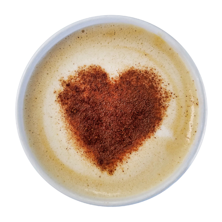 Heart made of cinnamon powder on top of cappuccino foam isolated over white background.