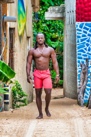 Young handsome shirtless African American man walking.
