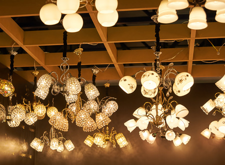 diamond candle: A lot of beautiful chandeliers with glass shades hanging from the ceiling in the sales area